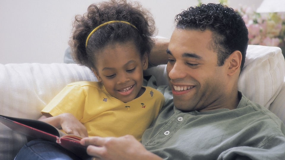 A father and daughter reading